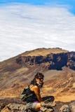 Frau mit einem Rucksack, der am Rand der Klippe auf dem Ba sitzt Lizenzfreie Stockfotografie