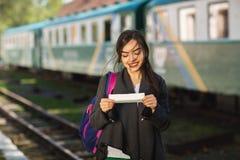 Frau mit einem Rucksack, nahe dem Zug ?berpr?ft seine Karte zur Stationsplattform lizenzfreie stockfotografie
