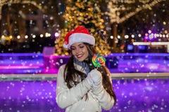 Frau mit einem Sankt-Hut vor einer Weihnachtseisbahn stockfotos