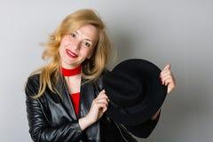 Frau mit einem schwarzen Hut auf einem Grau lizenzfreie stockbilder