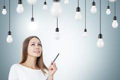 Frau mit einem Stift und Glühlampen Stockbilder