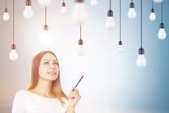 Frau mit einem Stift und Glühlampen, getont Lizenzfreie Stockfotos
