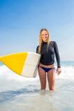 Frau mit einem Surfbrett an einem sonnigen Tag Lizenzfreie Stockbilder
