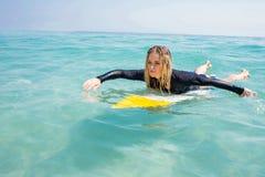 Frau mit einem Surfbrett an einem sonnigen Tag Lizenzfreies Stockfoto