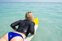 Frau mit einem Surfbrett an einem sonnigen Tag Stockbild