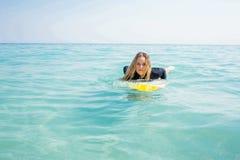 Frau mit einem Surfbrett an einem sonnigen Tag Stockfotografie
