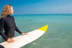 Frau mit einem Surfbrett an einem sonnigen Tag Stockfoto