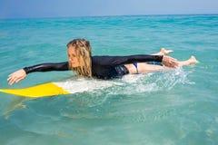 Frau mit einem Surfbrett an einem sonnigen Tag Lizenzfreie Stockfotos