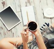 Frau mit einem Tasse Kaffee, einem Notizblock und einer Tablette Lizenzfreie Stockbilder