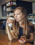 Frau mit einem trinkenden Kaffee und einem Denken des Mobiltelefons Stockbild