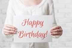 Frau mit einem Zeichen in ihren Händen mit alles Gute zum Geburtstag der Wörter Stockbild