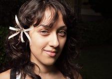 Frau mit einer Blume hinter ihrem Ohr Stockbild