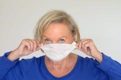 Frau mit einer chirurgischen Maske Stockfotos