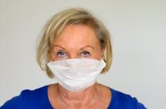 Frau mit einer chirurgischen Maske Stockfotografie