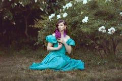 Frau mit einer Flieder sitzt auf dem Gras stockfotografie