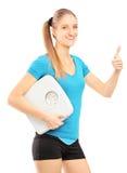 Frau mit einer Gewichtsskala, die Daumen aufgibt Stockbild