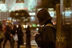 Frau mit einer Gitarre auf ihr zurück simsend auf der Straße in Shibuya, Tokyo, Japan Lizenzfreie Stockbilder