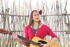 Frau mit einer Gitarre und einer roten Rose in ihrem Haar stockfotografie
