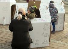 Frau mit einer Kinderfarbe auf dem Kasten stockbilder