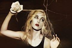 Frau mit einer Rose in seiner Hand Lizenzfreie Stockbilder