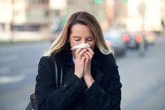 Frau mit einer Saisonwinterkälte, die ihre Nase durchbrennt stockfoto