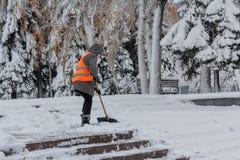 Frau mit einer Schaufel in einer orange Weste säubert Schnee Stockfotos
