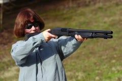 Frau mit einer Schrotflinte mit 12 Lehren Stockfotografie