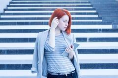 Frau mit einer Tablette in den Händen, die beiseite auf dem Hintergrund der Treppe im Geschäftszentrum schauen Stockbild