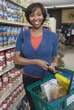 Frau mit Einkauf im Supermarkt Stockbild