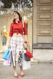 Frau mit Einkaufen-Beuteln lächelnd am Speicher Lizenzfreie Stockfotografie