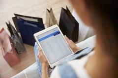 Frau mit Einkaufstasche-Kontrollbankauszug auf Digital-Tablet stockfotos