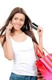 Frau mit Einkaufstaschekreditkarte in der Hand sprechend auf Zelle Lizenzfreie Stockfotos