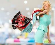 Frau mit Einkaufstaschen im Bekleidungsgeschäft Stockfotografie
