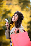 Frau mit Einkaufstaschen und Kreditkarte im Herbst Stockfotografie