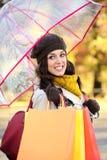 Frau mit Einkaufstaschen unter Herbstregen Stockfotografie
