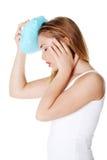 Frau mit Eisbeutelhebenkopfschmerzen Stockbild