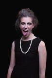 Frau mit elegantem schwarzem Kleid, mit seinem Zunge ou stockfotografie