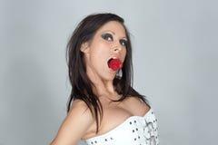 Frau mit Erdbeere im Mund Lizenzfreies Stockfoto