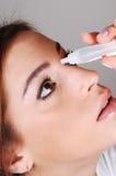 Frau mit eyedrops. Stockbild