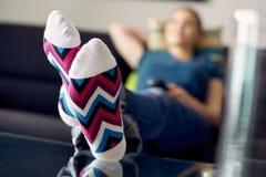 Frau mit Füßen im Tabellen-aufpassendem Film Fernsehen zu Hause Stockbild