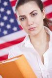 Frau mit Faltblatt über amerikanischer Flagge Lizenzfreie Stockbilder