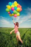 Frau mit Feld der Spielzeugballone im Frühjahr Stockfoto