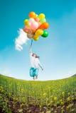 Frau mit Feld der Spielzeugballone im Frühjahr Stockfotografie