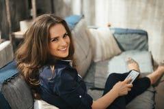 Frau mit Fernsehfernsteuerungsentspannung auf Sofa in der Dachbodenwohnung Stockbilder