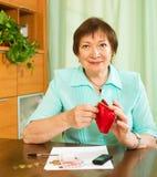 Frau mit Finanzdokumenten und Geld Stockfotografie