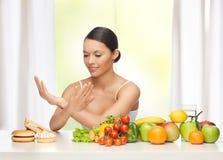 Frau mit Früchten ungesunde Fertigkost zurückweisend Stockbild