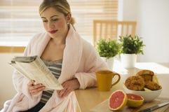 Frau mit Frühstück und Zeitung in der Küche Stockbilder