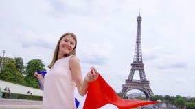 Frau mit französischer Flagge nahe Eiffelturm in Paris Glückliche lächelnde touristische Frau, die in Europa reist stock video