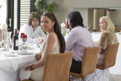 Frau mit Freunden am Abendessen Stockbilder