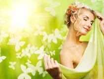 Frau mit frischen Blumen in ihrem Haar. Lizenzfreie Stockfotos
